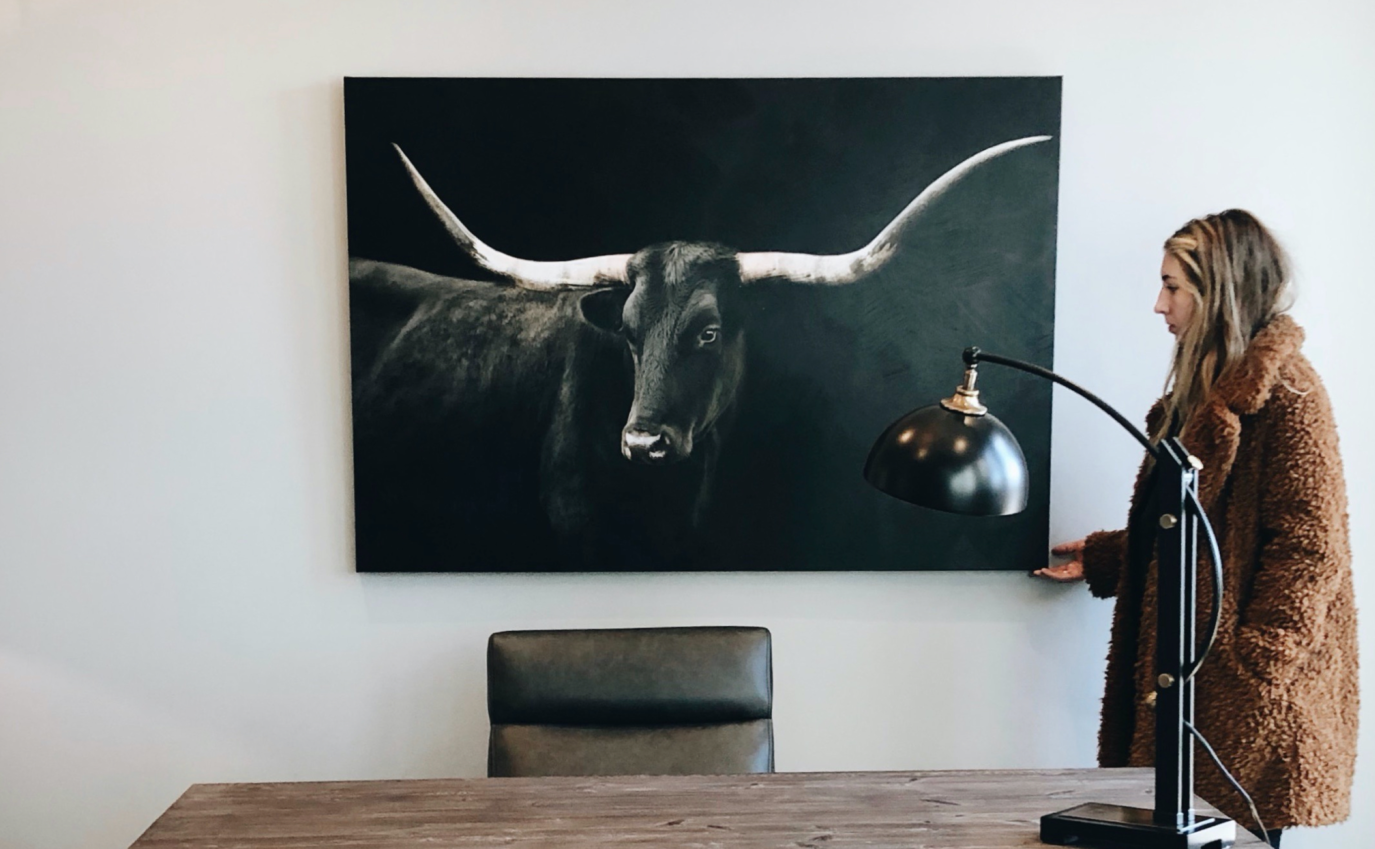 woman with painting of bull in office